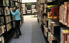 Stack it up! National Junior Honor Society member Vanessa Roman organizes shelves of books for volunteer hours at the Altoona Area Library. She was working to complete the 20 hours of community service required for ninth grade students in NJHS.
