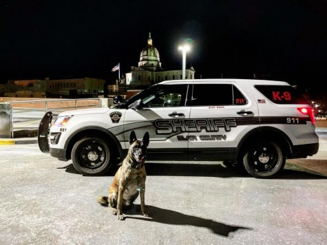On patrol! K-9 Rik relaxes during his shift posing by his new police ride on a crisp night. Corporal Bennett received the public vehicle through helpful donations.