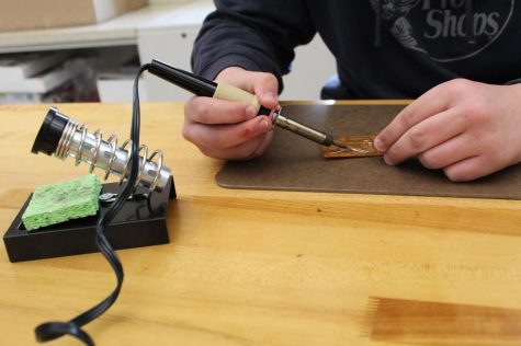 "Priority first! Eighth grader Seth Goheen works on a small circuit while wielding a soldering iron. Students' measurements and actions must be extremely precise, as one mistake could render the circuit inoperable. ""It was definitely fun, one of my favorite units,"" explained Goheen."