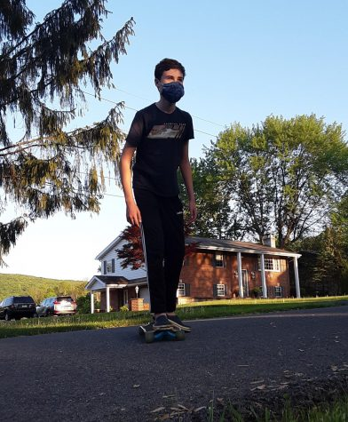 On the move! Sixth grader, Jonathan Slusser, rides on a skateboard earlier this week. He skated long before skateboarding became more popular.  Slusser said, I think that it is convenient to carry around, fun to ride and a great way to hangout with friends.